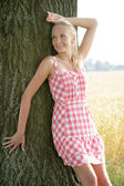 Young woman leaning agaisnt a tree — Stock Photo