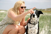 Young blonde woman with dog — Stok fotoğraf