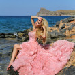 Beautiful blond woman with long legs in a pink ball gown — Stock Photo