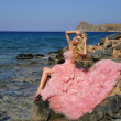 Beautiful blond woman sexy pink ballroom dress standing on the rocks in Santorini — Stock Photo