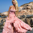 Beautiful blond woman sexy pink ballroom dress standing on the rocks in Santorini — Stock Photo #35256269