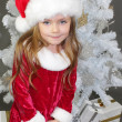 Girl in red dressed as Santa Claus with Christmas tree — Stock Photo #35257873