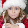 Girl in red dressed as Santa Claus with Christmas tree — Stock Photo