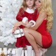 Mom and daughter with Christmas gifts at Christmas tree — Stock Photo