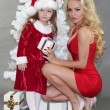 Mom and daughter with Christmas gifts at Christmas tree — Стоковое фото