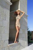 Beautiful blond woman with long legs in the fleshy crystal dress — Stock Photo