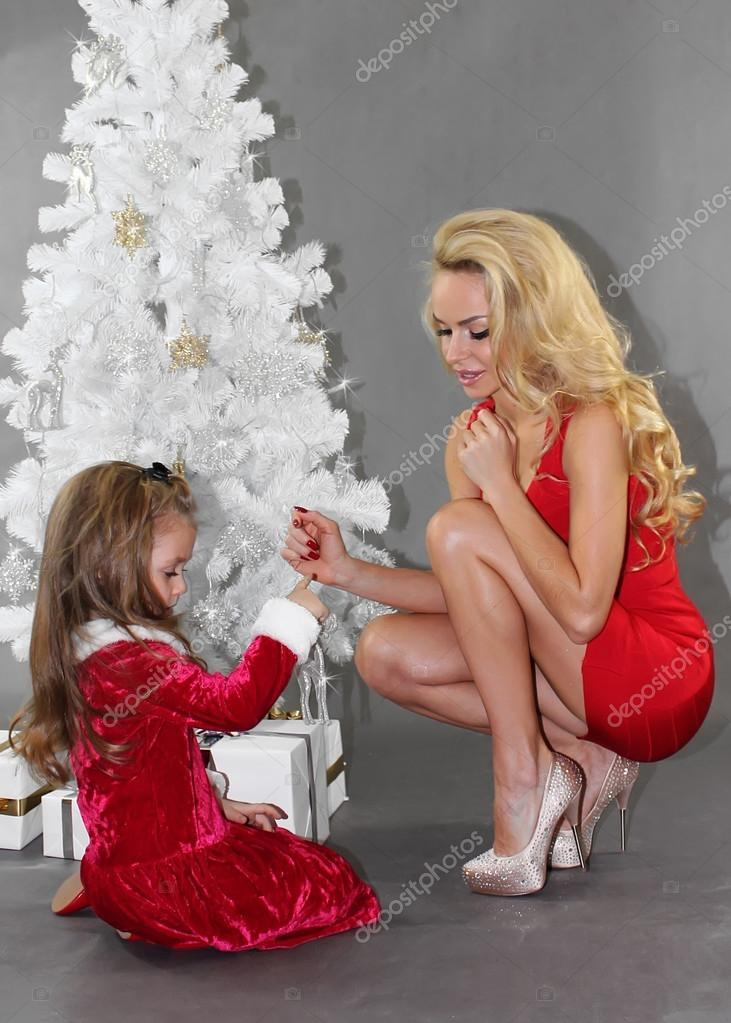 Mom And Daughter With Christmas Gifts At Christmas Tree