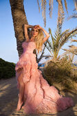 Beautiful blond woman with long legs in a pink ball gown — ストック写真