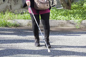 Close up in blind woman's feet with stick — Stock Photo