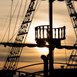 Постер, плакат: Silhouette of sails of an antique ship masts and bowsprit of a