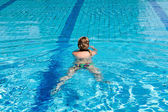 Jovem mulher com maiô nadar numa piscina de água azul — Fotografia Stock