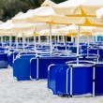 Sunchairs and umbrellas on beach bar — Stock Photo #47178331