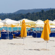 Closed parasols on the beach with sunchairs and umbrellas in the — Stock Photo #47178337