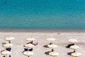Beach with tourists, sun beds and umbrellas. Expected to be the  — Stock Photo