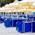 Sunchairs and umbrellas on beach bar — Stock Photo #47406949