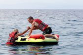 Unrecognized man helping woman to get on water inflatable. 20 mi — Stock Photo