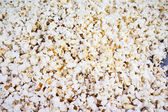 Salted popcorn grains on the white background — Stok fotoğraf