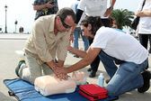 People practicing CPR on a mannequin, with the instructor's help — Stock Photo