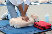 Female instructor showing CPR on training doll — Stock Photo