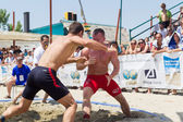 Two male athletes wrestle on sand during the First World Champio — ストック写真