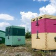 Beehives at green field against cloudy sky. — Stock Photo #51147159