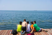 Kids sitting on wooden platform beside polluted sea with clear s — Stock Photo