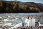 Decorei casamento mesa com cadeiras, em pé no rio — Foto Stock