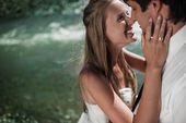 Beautiful wedding couple hugging and smiling on the river — Stockfoto