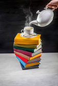 Stack of colorful books with a cup of tea on it and teapot pouri — Stock Photo