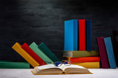 Opened book on the table with glasses and another colorful books — Stock Photo