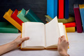 Reading book on white table with another color books on backgrou — Stock Photo