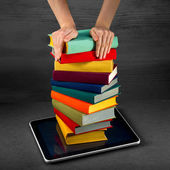Putting or download colorful books to the tablet — Stock Photo
