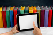 Reading on the tablet with colorful books on background — Stock Photo