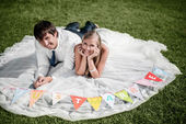 "Smiling wedding couple lying on the grass with ""just married"" fl — Stock Photo"