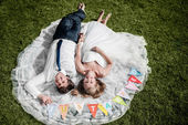 "Smiling wedding couple lying on the grass with ""just married"" fl — Stockfoto"