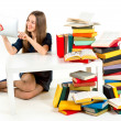 Stock Photo: Girl reading something on tablet with heaps of unnecessary books