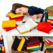 Stock Photo: Young girl fell asleep on heap of colored books on white backgro