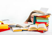 Girl hiding behind stack of colorful books and smiling — Stock Photo