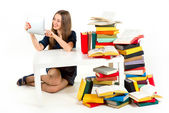 Girl reading something on tablet with heaps of unnecessary books — Stock Photo