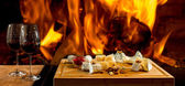 Delicious cheese and wine at the fireplace — Foto de Stock