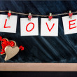 Paper cards with letters LOVE attached with clothes pins on the — Stock Photo