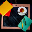 Books with tea on chalkboard with space for text — Stock Photo