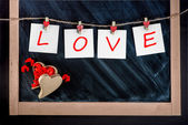 Paper cards with letters LOVE attached with clothes pins on the — Foto Stock