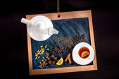 Cup of tea and teapot with spices and lemon on chalkboard on bla — Stock Photo