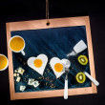 Breakfast with eggs, cheese, kiwi and orange juice on chalkboard — Stock Photo #43106731