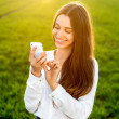 Young woman laughing and typing message in smart phone in the gr — Stock Photo #43127367