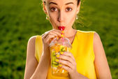 Young woman drinking fruits from the transparent cup on green gr — Stock Photo