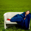 Girl sleeping with the book on the couch in the green field — Stock Photo