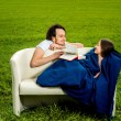 Man take care about his girlfriend on the couch on the green fie — Stock Photo #43931473