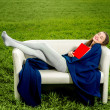 Girl sleeping or dreaming with the book on the couch in the gree — Stock Photo